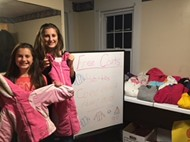 Bella and Grace LeBarron sort donated coats