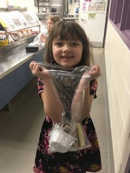 First grader Kaitlyn H. picks up her breakfast to bring to her classroom.