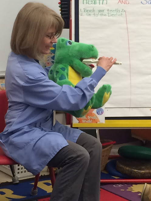Liz Spooner uses a Gator to teach tooth brushing to young children.